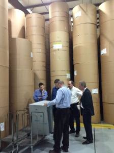 Members of the SBJ staff stand among more than 600, 1,200-pound rolls of newsprint stacked floor to ceiling during the Feb. 8 tour.