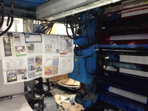 Proof copies of SBJ's Feb. 11-17 issue hang alongside the press as workers align printing plates on the massive two-story machine.