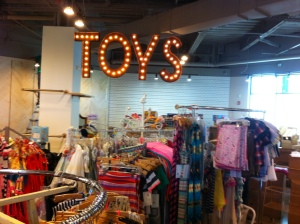 "A large ""toys"" sign hangs above the clothes at Jellybeans."