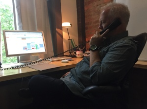 """Back at the office after lunch, Shawn sits in on a conference call. He tells me the company recently got a new phone system and he's """"still learning all the new buttons."""""""